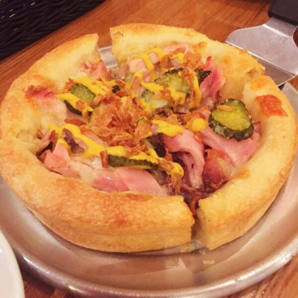 「デビルクラフト浜松町店」の季節のシカゴピザ(Sサイズ)。ピクルス、ハム、マスタードなどを使用した珍しい味わいのピザでした。