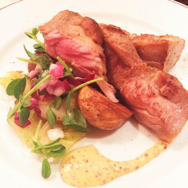 銀座・東銀座エリアにある人気ビストロ「パリのワイン食堂」の「フランスブルターニュ産 豚肩ロースのステーキ 粒マスタードソース」
